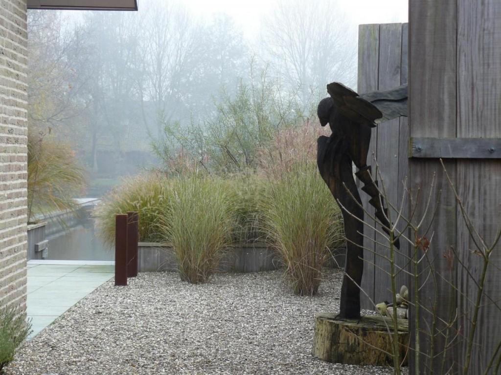 Laaghangende mist zorgt voor mystiek in deze moderne tuin aan het water