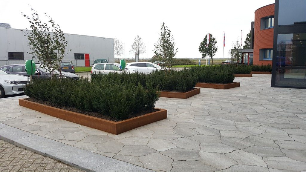 De langwerpige cortenstaal bloembakken verwijzen naar de 'groene' bakstenen waarmee het bedrijf duurzaam bouwt