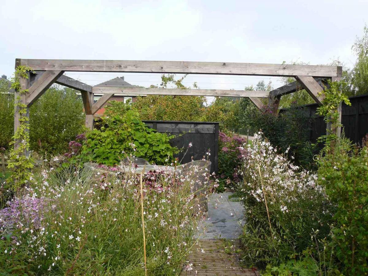 Robuuste pergola en rustieke schutting geven tuin extra body for Schutting tuin
